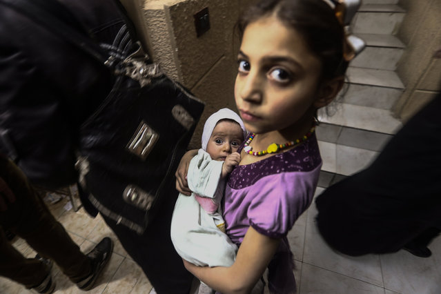 A little girl holding her newborn sister waits for their turn in a queue during a vaccination campaign under the supervision of the Syrian Arab Red Crescent (SARC) humanitarian nonprofit organization, in the besieged Syrian town of Douma, Syria, 23 May 2017. According to a statement from SARC, in the city of Douma some 12,809 children under the age of five were immunized in a vaccination campaign to prevent measles and poliomyelitis. The campaign was the first of its kind with the participation of 100 volunteers. SARC has been delivering vaccines to 17 health centers approved for vaccination campaigns in towns and villages in the Eastern Ghouta area. (Photo by Mohammed Badra/EPA)