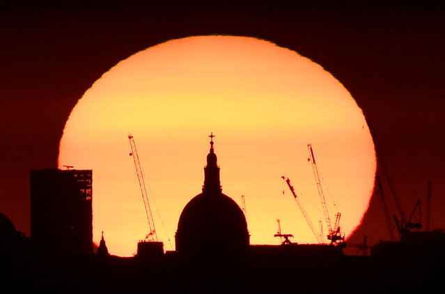 The dome of St Paul's Cathedral and construction cranes are silhouetted by the rising sun at dawn in London, Britain, August 5, 2018. (Photo by Toby Melville/Reuters)