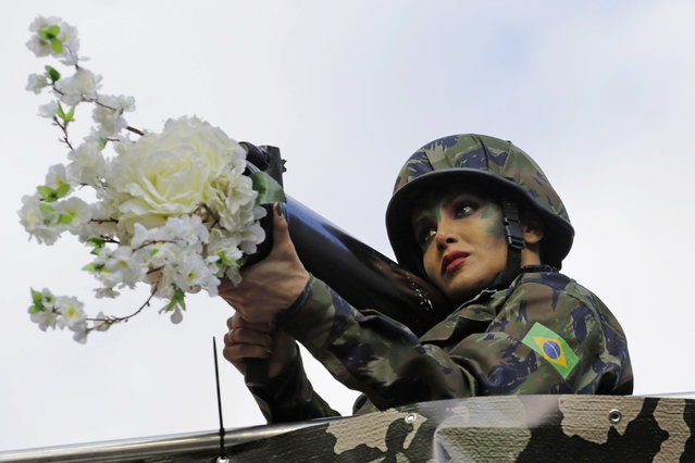 A reveler, dressed as a Brazilian national army soldier holding a mock weapon with flowers jutting out of it, participates in the annual Gay Pride Parade in Sao Paulo, Brazil, Sunday, June 18, 2017. (Photo by Nelson Antoine/AP Photo)