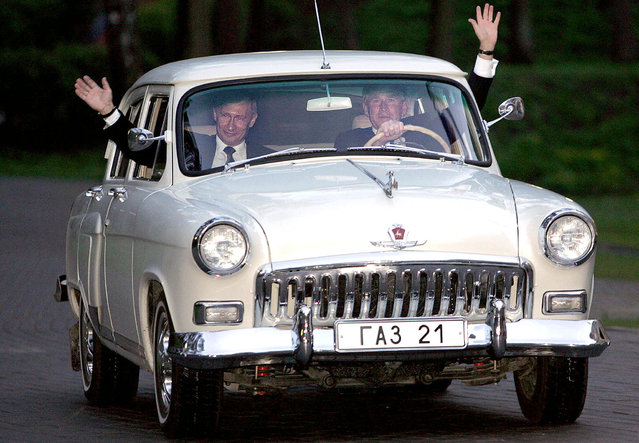 "US President George W. Bush (R) and Russian President Vladimir Putin wave as the two presidents go for a ride in Putin's 1956 Volga before dinner 08 May 2005 at the his residence outside of Moscow. Bush hailed Russia's ""bravery and sacrifice"" in defeating Nazism, as he met Putin ahead of ceremonies marking the 60th anniversary of the end of World War II. Bush, who the previous day criticized the decades-long Soviet occupation of central Europe, said he was looking forward to the 09 May ceremony on Moscow's Red Square, to be attended by over 50 national leaders. (Photo by Tim Sloan/AFP Photo)"