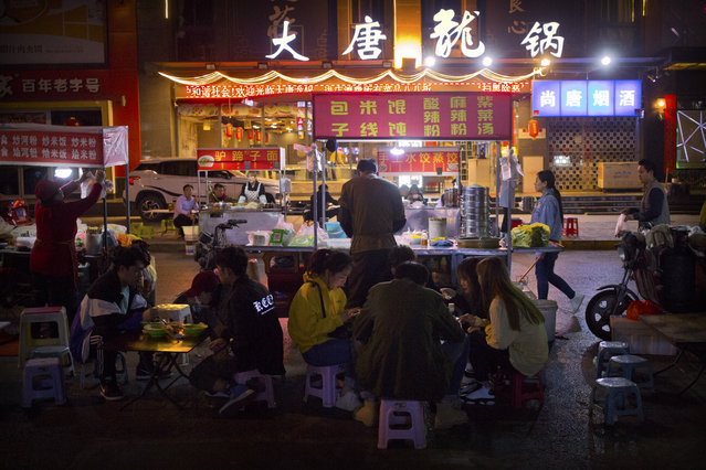 In this March 27, 2019, photo, people eat at an outdoor night market in Xi'an, northwestern China's Shaanxi Province, similar to one at which Yin Hao, who also goes by Yin Qiang, was injured during a fight that led to his initial prescription for Tylox. Officially, pain pill abuse is an American problem, not a Chinese one. But people in China have fallen into opioid abuse the same way many Americans did, through a doctor's prescription. And despite China's strict regulations, online trafficking networks, which facilitated the spread of opioids in the U.S., also exist in China. (Photo by Mark Schiefelbein/AP Photo)