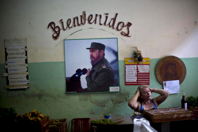 """In this December 26, 2014 file photo, a photograph of Fidel Castro hangs under the Spanish word """"Welcome"""" on the wall at a state-run food market in Havana, Cuba. (Photo by Ramon Espinosa/AP Photo)"""