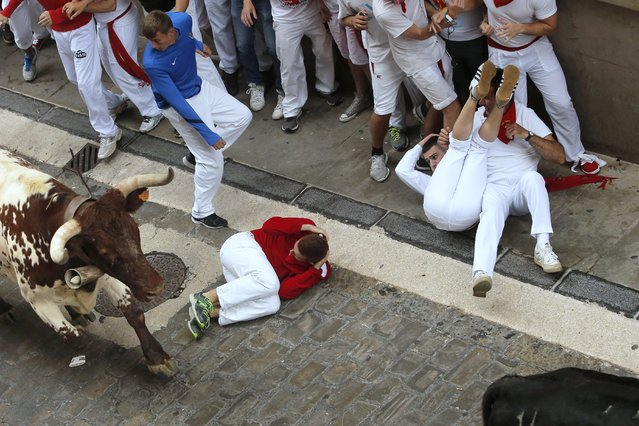 Revelers fall as Torrestrella fighting bull run during the running of the bulls of the San Fermin festival, in Pamplona, Spain, Monday, July 7, 2014. (Photo by Andres Kudacki/AP Photo)