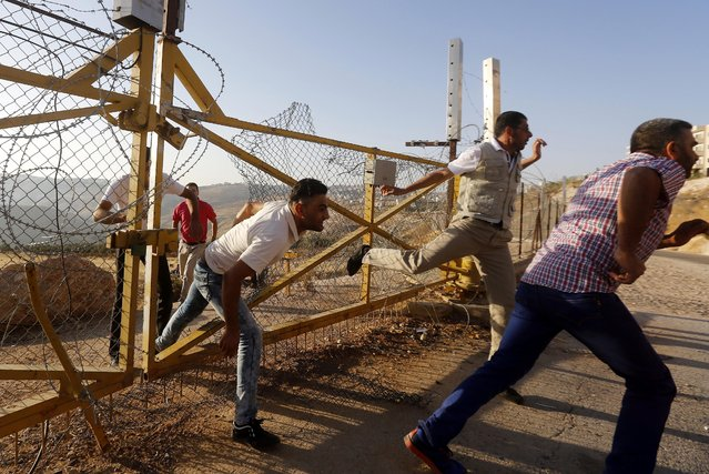 Young Palestinian men climb through a barb wire enforced barrier fence near the West Bank city of Bethlehem, in an attempt to enter Jerusalem to attend the second Friday prayers in the Muslim holy month of Ramadan at the al-Aqsa Mosque in the Muslim holy month of Ramadan, 17 June 2016. Israeli authorities the week before only allowed access to Jerusalem for women and children and limited the age of men to those over 45. (Photo by Abed Al Hashlamoun/EPA)