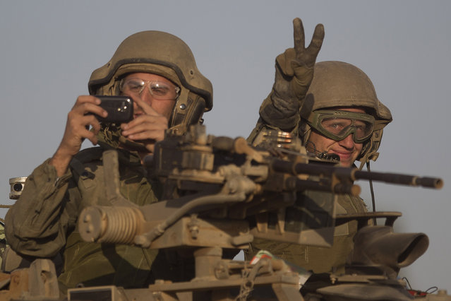 Israeli soldiers ride on a tank to a position near Israel Gaza Border, Thursday, July 10, 2014. With rockets raining deep inside Israel, the military pummeled Palestinian targets Wednesday across the Gaza Strip and threatened a broad ground offensive, while the first diplomatic efforts to end two days of heavy fighting got underway. (Photo by Ariel Schalit/AP Photo)