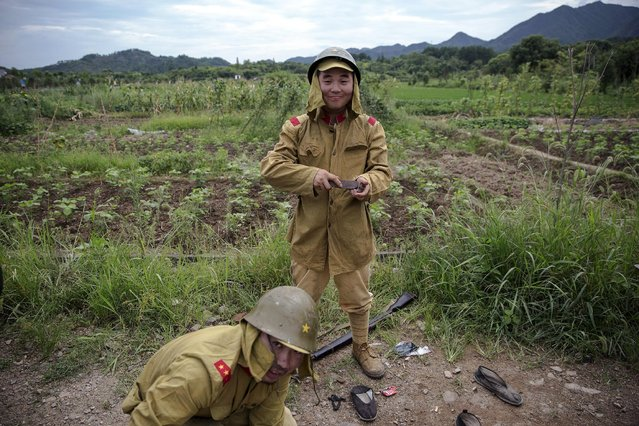 """Actors get dressed in historical Japanese army uniform costumes, minutes after playing small roles as Chinese soldiers on the set of """"The Last Prince"""" television series on location near Hengdian World Studios near Hengdian July 24, 2015. (Photo by Damir Sagolj/Reuters)"""