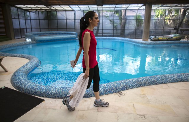 Educationalist and model Fatima walks past the swimming pool after working out in her gym at her house in Lahore May 28, 2014. Fatima is the CEO of PDLC Beaconhouse, and her mother-in-law is the founder of Beaconhouse School System, a network of schools. (Photo by Zohra Bensemra/Reuters)