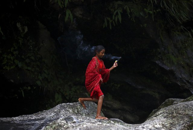 """A Hindu devotee holding incense walks along the bank of Bagmati River while participating in the """"Bol Bom"""" pilgrimage in Kathmandu August 10, 2015. (Photo by Navesh Chitrakar/Reuters)"""