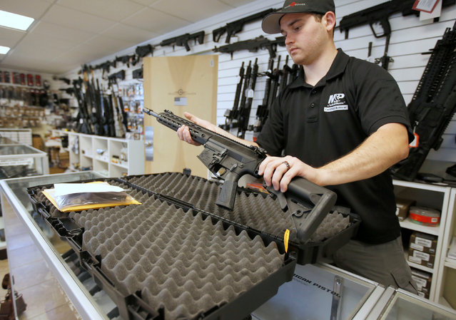 """Salesman, Ryan Martinez  takes an AR-10 out of it's case at the """"Ready Gunner"""" gun store in Provo, Utah, U.S., June 21, 2016. (Photo by George Frey/Reuters)"""