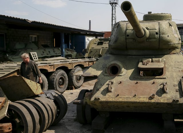 A worker walks pass an old soviet tank T-34 (R) as he fixes military vehicle (L) at Phaeton museum in Zaporizhia, Ukraine, August 11, 2015. (Photo by Gleb Garanich/Reuters)