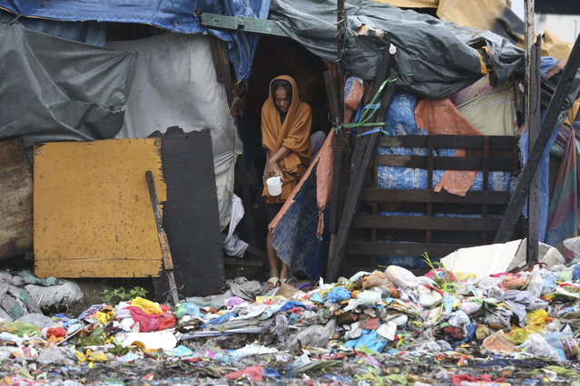 A Filipino woman keeps herself warm by using a blanket as she looks from inside her makeshift home while Typhoon Rammasun nears suburban Navotas, Philippines, Wednesday, July 16, 2014. Rammasun knocked out power in many areas but it spared the Philippine capital, Manila, and densely-populated northern provinces from being directly battered Wednesday when its fierce wind shifted slightly away, officials said. (Photo by Aaron Favila/AP Photo)
