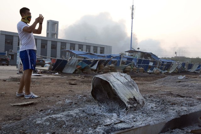 A man takes a photo near a burnt drum that residents said flew from a nearby explosion seen in the background in northeastern China's Tianjin municipality, Thursday, August 13, 2015. Huge explosions sparked overnight at a warehouse for dangerous materials in the northeastern Chinese port of Tianjin killed at least 13 people, injured hundreds and sent massive fireballs into the night sky, officials and state media outlets said Thursday. (Photo by Ng Han Guan/AP Photo)