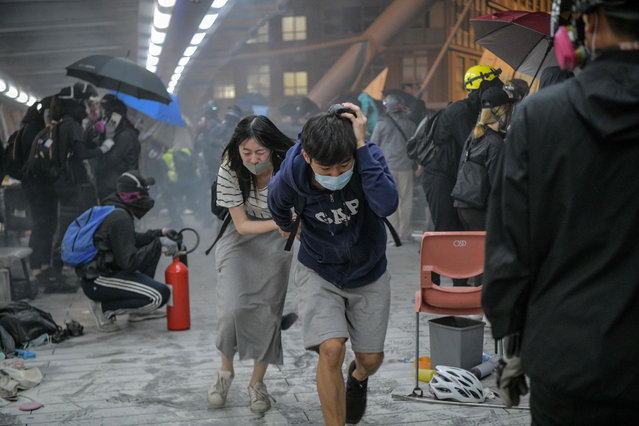 Protesters run for cover after riot police fired tear gas towards the bridge they were climbing down to the road below, to escape from Hong Kong Polytechnic University campus and from police, in Hung Hom district in Hong Kong on November 18, 2019. Dozens of Hong Kong protesters escaped a besieged university campus on November 18 by lowering themselves on a rope from a footbridge to a highway, AFP video showed. Once on the road they were seen being picked up by waiting motorcyclists. (Photo by Anthony Wallace/AFP Photo)