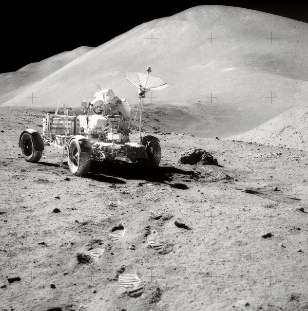 David R. Scott, Commander of Apollo 15, works at the Lunar Roving Vehicle (LRV) during the third lunar surface extravehicular activity (EVA) of the mission at the Hadley-Apennine landing site. Hadley Rille is at the right center of the picture. Hadley Delta, in the background, rises approximately 4,000 meters (about 13,124 feet) above the plain. St. George Crater is partially visible at the upper right edge. This photograph was taken by Lunar Module pilot James B. Irwin. This view is looking almost due South. (Photo by NASA)