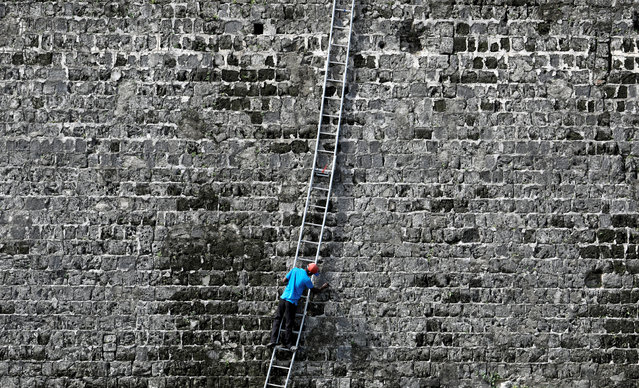 A worker cleans a wall at the Jaffna Fort, a fort built by the Portuguese in 1618, in Jaffna, Sri Lanka on August 25. 2019. (Photo by Dinuka Liyanawatte/Reuters)