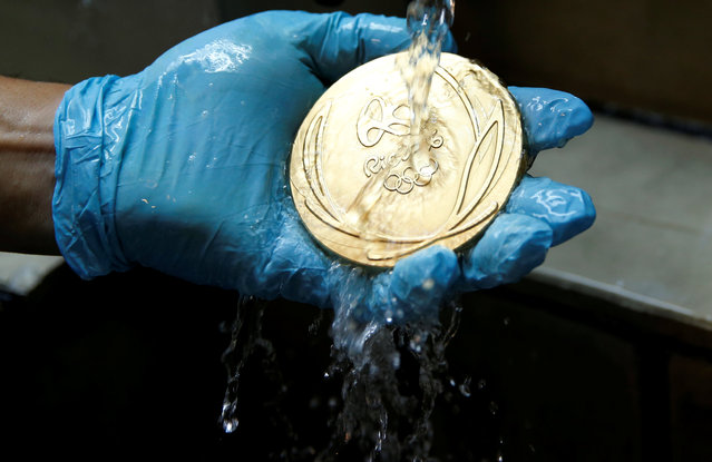 A worker from the Casa da Moeda do Brasil (Brazilian Mint) cleans a Rio 2016 Olympic medal in Rio de Janeiro, Brazil, June 28, 2016. (Photo by Sergio Moraes/Reuters)