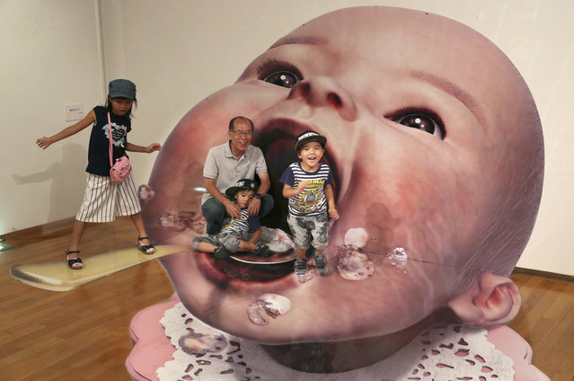 Visitors pose for a photo with a 3D image at a 3D trick art exhibition by Japanese artist Masashi Hattori in Kawasaki, near Tokyo, Saturday, Aug. 5, 2017. (Photo by Koji Sasahara/AP Photo)