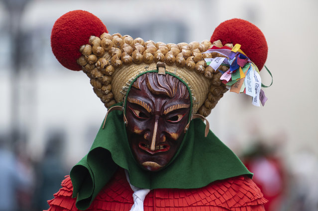 A fool of the Elzacher Schuttig walks through the main street during the traditional Schuttig jump carnival parade in Elzach, Germany, Sunday, February 23, 2020. (Photo by Patrick Seeger/dpa via AP Photo)