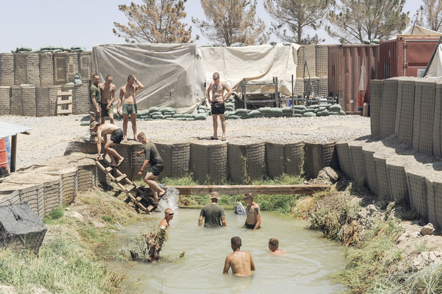 Moments of leisure are prized. Marines swim in an irrigation canal at their outpost in Helmand Province, Afghanistan. The same day, a patrol from another base was hit by an IED. (Photo and caption by Van Agtmael/Harrison Jacobs/Magnum Photos)
