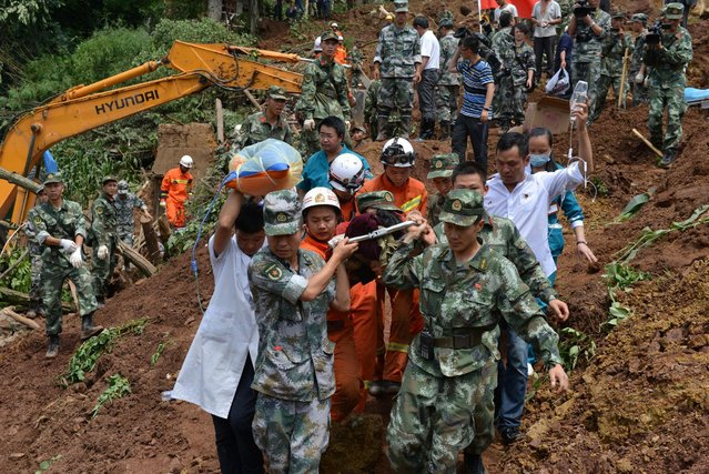 Rescue workers carry a victim from the site of a landslide in Bijie, Guizhou province, China, July 1, 2016. (Photo by Reuters/Stringer)