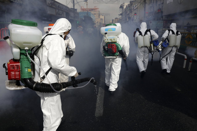 Firefighters disinfect a street against the new coronavirus, in western Tehran, Iran, Friday, March 13, 2020. The new coronavirus outbreak has reached Iran's top officials, with its senior vice president, Cabinet ministers, members of parliament, Revolutionary Guard members and Health Ministry officials among those infected. The vast majority of people recover from the new coronavirus. According to the World Health Organization, most people recover in about two to six weeks, depending on the severity of the illness. (Photo by Vahid Salemi/AP Photo)