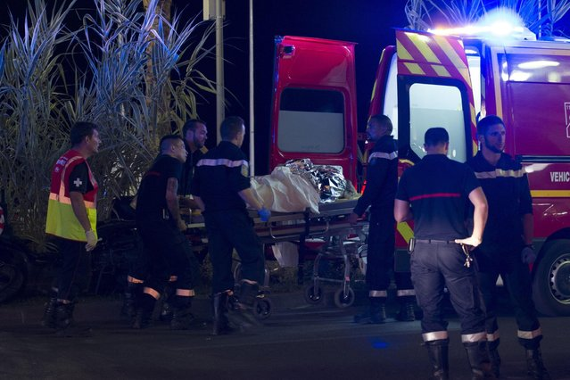 Wounded people are evacuated from the scene where a truck crashed into the crowd during the Bastille Day celebrations in Nice, France, 14 July 2016. According to reports, at least 70 people died and many were wounded after a truck drove into the crowd on the famous Promenade des Anglais during celebrations of Bastille Day. Anti-terrorism police took over the investigation in the incident, media added. (Photo by Olivier Anrigo/EPA)