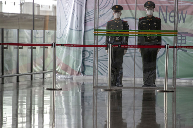 In this March 12, 2020, photo, Chinese paramilitary policemen stand on duty behind a barrier at the Capital International Airport terminal 3 in Beijing. As the number of new cases dwindles in China and multiplies abroad, the country once feared as the source of the COVID-19 outbreak is now worried about importing cases from abroad. China hasn't imposed any travel bans, but Beijing said this week that all people arriving from overseas would have to self-quarantine for 14 days. (Photo by Ng Han Guan/AP Photo)