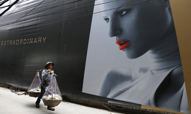 A Thai street food-seller walks the streets passing a high-end, luxury shopping center construction site boarded with advertisements of fashion models, in Bangkok, Thailand, August 21, 2014. (Photo by Barbara Walton/EPA)