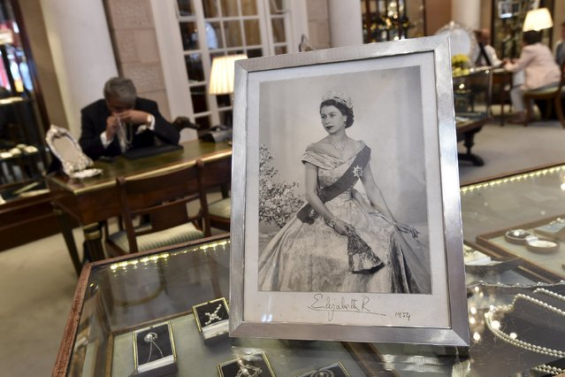 A hand-signed portrait of Queen Elizabeth is seen as jeweller Omar Vaja views the quality of diamonds through a lupe at Bentley and Skinner in central London, Britain, August 19, 2015. Bentley and Skinner, established in the 19th century, is a silversmith and jeweller to Queen Elizabeth. (Photo by Toby Melville/Reuters)