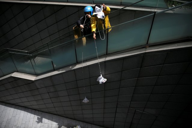 Delivery workers pull ropes to pick up food from restaurants as the nearest entrance to downstairs has been blocked following the novel coronavirus disease (COVID-19) outbreak, at the Galaxy Soho office buildings in Beijing, China on April 16, 2020. (Photo by Tingshu Wang/Reuters)