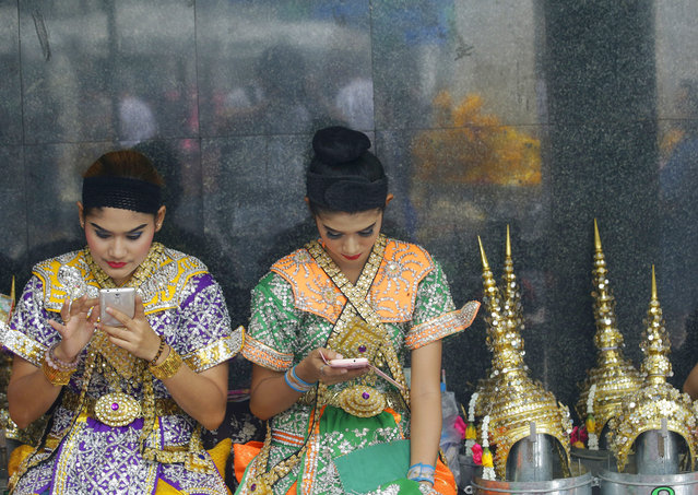 Thai classical dancers, who perform for Phra Phrom, which is the Thai interpretation of the Hindu god Brahma, use their mobile phones at the Erawan Shrine in Bangkok, Thailand, Thursday, September 3, 2015. (Photo by Sakchai Lalit/AP Photo)