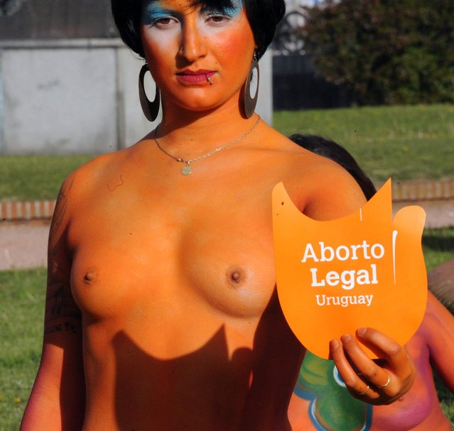 """A woman with a body painting and a sign reading """"Legal abortion"""", takes part in a demo in favour of the legalization of abortion in front of the Congress building in Montevideo on September 25, 2012. The Congress is voting a law project which would decriminilize the interruption of pregnancy under certain conditions, including obliging women to set out before a tribunal the reasons for the abortion.  AFP PHOTO/Miguel ROJO        (Photo credit should read MIGUEL ROJO/AFP/GettyImages)"""