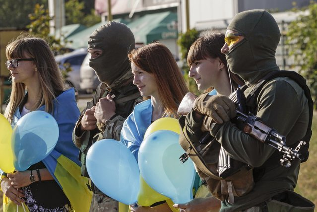 "People draped with national flags on their shoulders pose for a photo with armed Ukranian soldiers during a pro-Ukranian meeting in the southern coastal town of Mariupol September 13, 2014. Ukraine's president said on Friday there could be no military solution to his country's crisis and said he hoped ""a very fragile"" ceasefire in the east would hold, allowing him to focus on rebuilding the shattered economy. (Photo by Vasily Fedosenko/Reuters)"