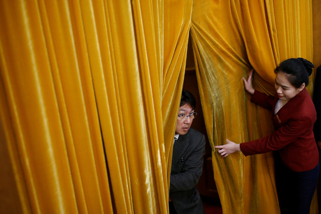 An usher lifts curtains for a man arriving to the Great Hall of the People during the opening session of the 19th National Congress of the Communist Party of China in Beijing, China on October 18, 2017. (Photo by Thomas Peter/Reuters)