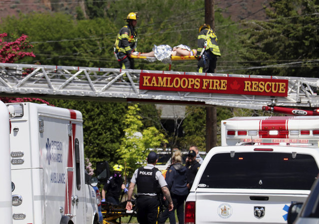 First responders carry an injured person on a stretcher across a fire truck ladder from a rooftop at the scene of a crash involving a Canadian Forces Snowbirds airplane in Kamloops, British Columbia, Sunday, May 17, 2020. (Photo by Brendan Kergin/Castanet Kamloops/The Canadian Press via AP Photo)