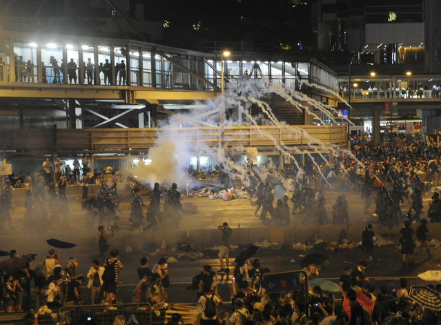 Riot police fire teargas to disperse protesters, after thousands of protesters blocked the main street to the financial Central district outside the government headquarters in Hong Kong September 28, 2014. (Photo by Reuters/Stringer)