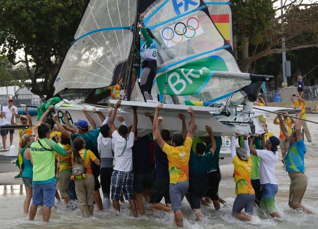 Members of the Brazilian sailing team carry the 49er FX women's boat after winning the gold medal at the 2016 Summer Olympics in Rio de Janeiro, Brazil, August 18, 2016. (Photo by Bernat Armangue/AP Photo)