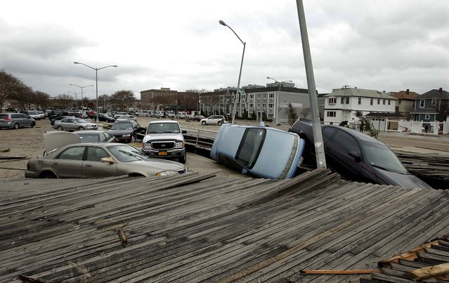Pedestrians walk past the boardwalk and cars displaced by superstorm Sandy near Rockaway Beach in Queens, N.Y. (Photo by Frank Franklin II/Associated Press)