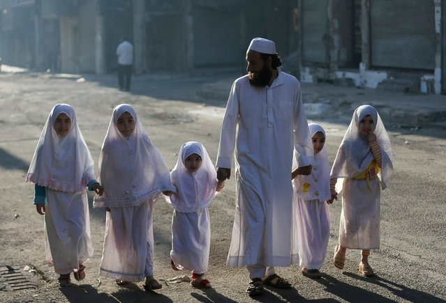 Children, accompanied by their father, walk together ahead of performing prayers on the first day of Eid al-Adha in the Duma neighbourhood in Damascus October 4, 2014. Muslims around the world celebrate Eid al-Adha to mark the end of the haj pilgrimage by slaughtering sheep, goats, camels and cows to commemorate Prophet Abraham's willingness to sacrifice his son, Ismail, on God's command. (Photo by Bassam Khabieh/Reuters)