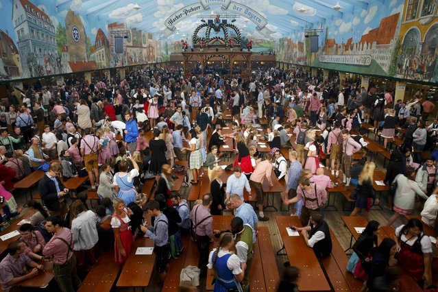 Customers take tables inside a tent after the opening of the 182nd Oktoberfest in Munich, Germany, September 19, 2015. (Photo by Michael Dalder/Reuters)