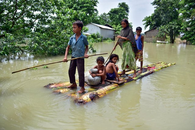 Villagers row a makeshift raft through a flooded field to reach a safer place at the flood-affected Mayong village in Morigaon district, in the northeastern state of Assam, India, June 29, 2020. (Photo by Anuwar Hazarika/Reuters)