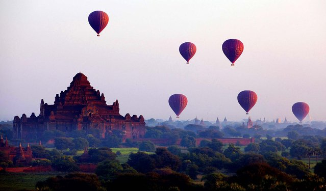 Balloons fly across some of Myanmar's 3,000 Buddhist temples during a sunrise flight in Bagan, November 13, 2012. (Photo by Mark Baker/Associated Press)