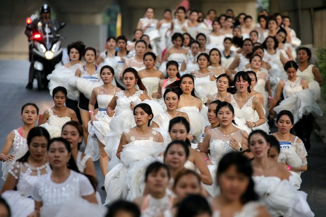 """Brides run while participating in the race during the """"Running of the Brides"""" race, in Bangkok, Thailand, December 2, 2017. (Photo by Athit Perawongmetha/Reuters)"""