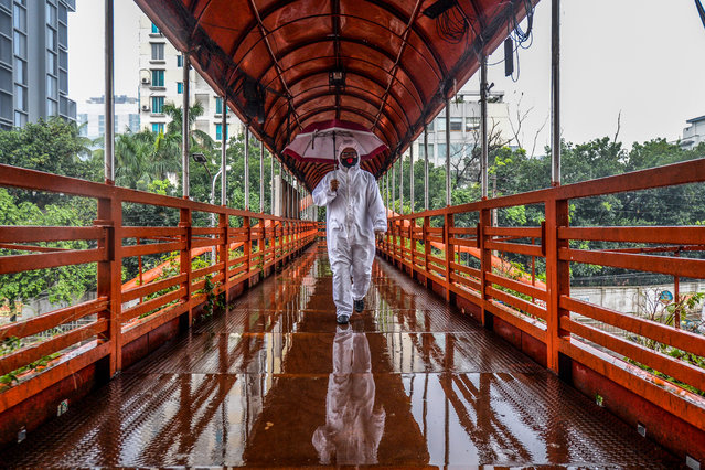 A man wearing protective gear as a preventive measure against the COVID-19 coronavirus walks over a footbridge in Dhaka on May 27, 2020. (Photo by Munir Uz Zaman/AFP Photo)