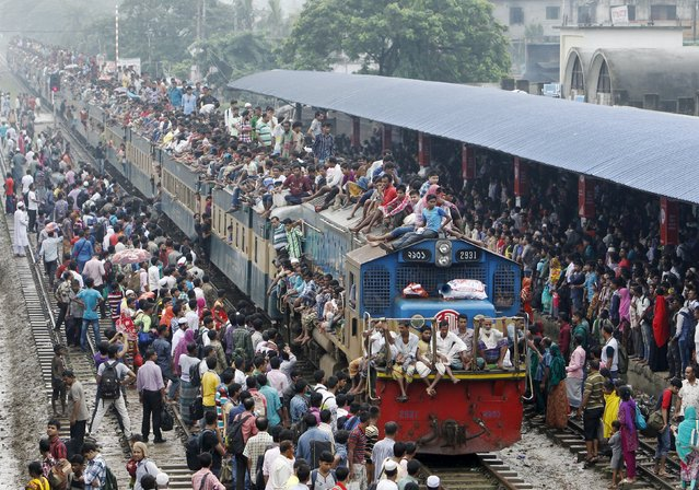People crowd on top of a train entering the Dhaka airport rail station September 24, 2015, as thousands of Bangladeshi Muslims head home to celebrate Eid-al-Adha. (Photo by Ashikur Rahman/Reuters)