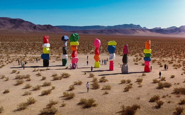 Visitors are dwarfed by brightly coloured sculptures comprising of stones that punctuate the stark, dry landscape of the Mojave desert in Nevada, USA on June 20, 2020. (Photo by Henry Do/Solent News)