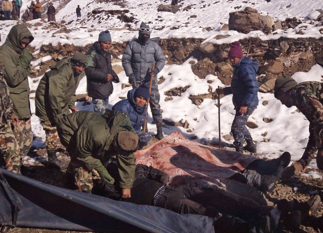 A handout picture released by the Nepalese Army shows members of the army pack dead bodies of trekkers from the Thorung La mountain pass on the Annapurna Circuit, in Mustang district, Nepal. 15 October 2014. (Photo by EPA/Nepalese Army)