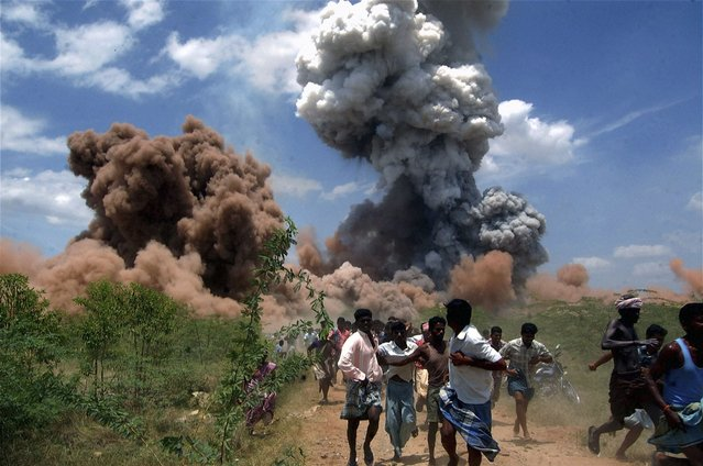 In this September 5, 2012 file photo, people run for cover as smoke rises from the site of a fire at a fireworks factory on the outskirts of Sivakasi, about 500 kilometers (310 miles) southwest of Chennai, India. Police in southern India arrested six employees of the fireworks factory for a massive blaze that killed 40 workers and injured 60 others. (Photo by AP Photo/File)