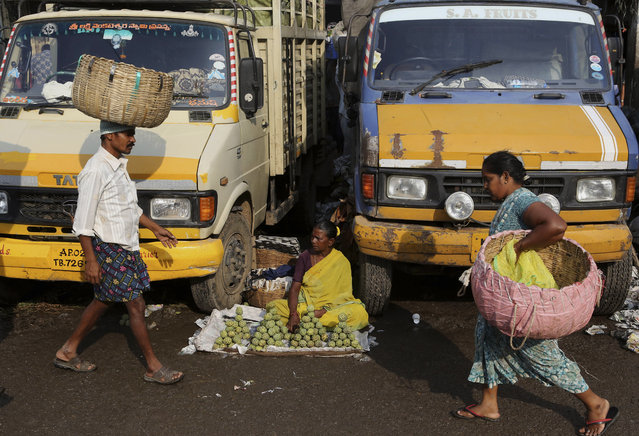 An Indian roadside vendor sits between trucks to sell fruits at a wholesale market in  Bangalore, India, Tuesday, September 29, 2015. India's central bank on Tuesday cut its key interest rate by half a percentage point, aiming to spur economic growth as inflation cooled to the lowest since November. (Photo by Aijaz Rahi/AP Photo)