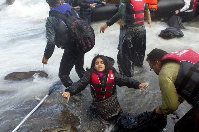 A migrant girl struggles to get out of the water as refugees and migrants arrive on an overcrowded dinghy in rough sea on the Greek island of Lesbos, after crossing a part of the Aegean Sea from the Turkish coast, October 2, 2015. (Photo by Dimitris Michalakis/Reuters)